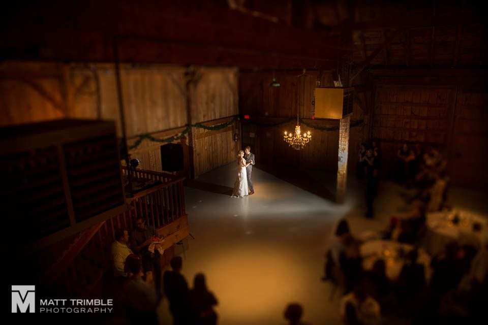 bride and groom enjoying first dance in barn