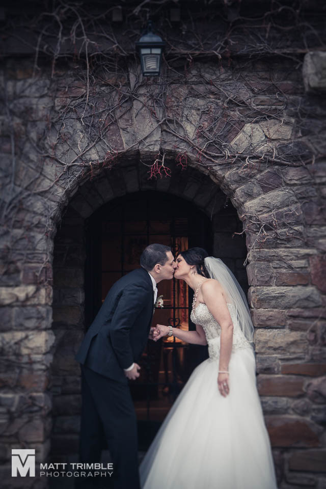 bride and groom kissing in entrance to bob rumball manor